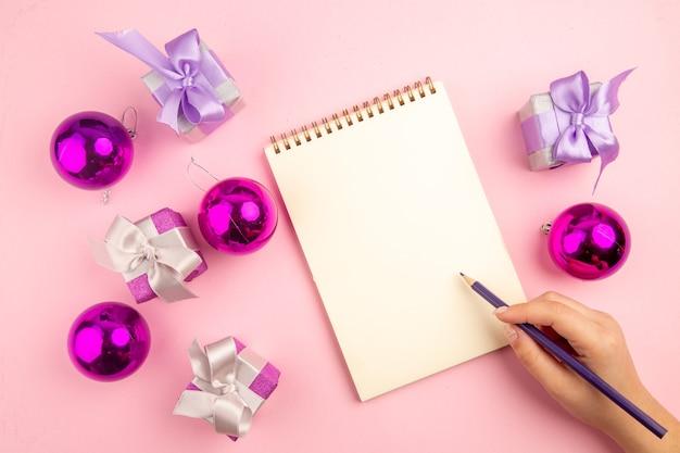 Vista superior de presentinhos com brinquedos de árvore de natal e bloco de notas na superfície rosa