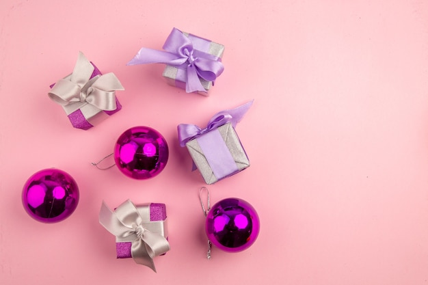 Vista superior de presentinhos com brinquedos de árvore de natal na superfície rosa