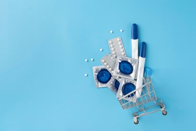 Vista superior de preservativos, pílulas e testes de gravidez