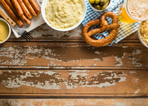 Vista superior de pretzels com cerveja e salsichas