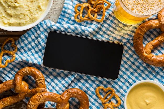 Vista superior de pretzels com cerveja e smartphone