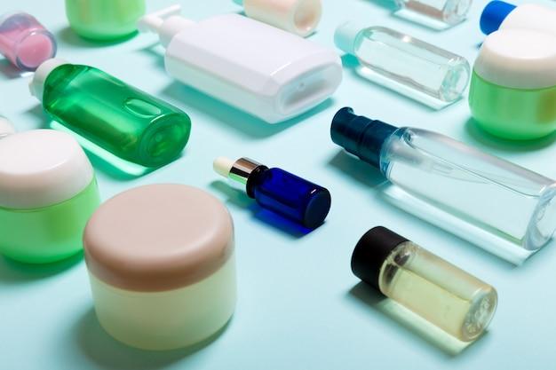 Vista superior de produtos cosméticos em diferentes frascos e garrafas em azul. close-up de recipientes com copyspace