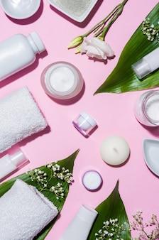 Vista superior de produtos cosméticos em fundo rosa com folhas e flores brancas.