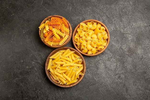Vista superior de produtos crus de composição de massas dentro de pratos no cinza