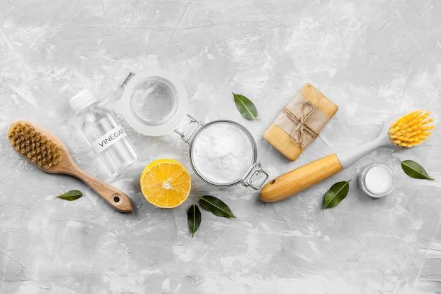 Vista superior de produtos de limpeza ecológicos com escovas e limão
