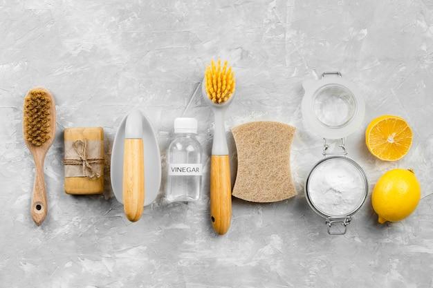 Vista superior de produtos de limpeza ecológicos com limão e escovas