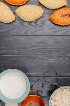 Vista superior de produtos de panificação, como shakarbura com farinha de aveia flocos de manteiga no fundo de madeira com espaço de cópia