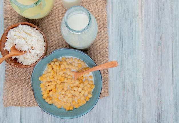 Vista superior de produtos lácteos como queijo cottage, leite condensado, leite de saco e fundo de madeira com espaço de cópia