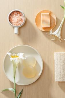 Vista superior de produtos orgânicos para a pele do spa com sal, flores, toalhas e sabonetes de arroz