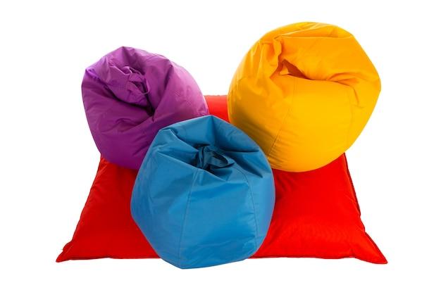 Vista superior de pufeiras roxas, azuis e amarelas no sofá pufe vermelho isolado no branco