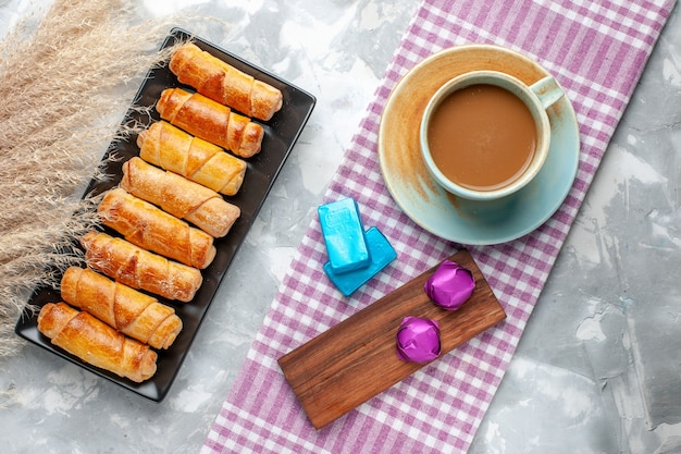 Vista superior de pulseiras assadas, deliciosos pastéis junto com café com leite em uma mesa leve, biscoitos doces