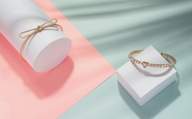 Vista superior de pulseiras douradas modernas sobre fundo geométrico cores pastel com sombra de folhas tropicais