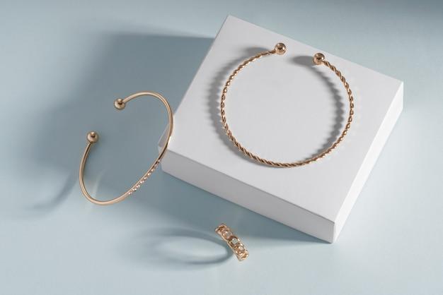 Vista superior de pulseiras e anéis de joias douradas na caixa branca sobre fundo de papel azul com espaço de cópia