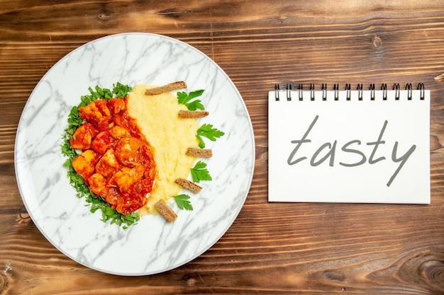 Vista superior de purê de batata com fatias de frango e palavra saborosa na mesa marrom