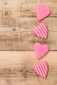 Vista superior de quatro bolinhos de gengibre em forma de coração em fundo de madeira retrô