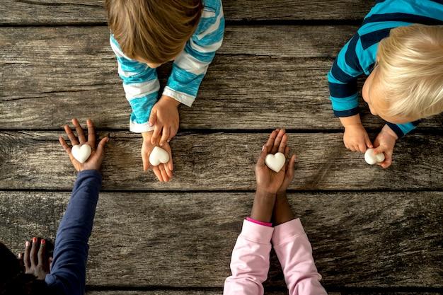 Vista superior de quatro crianças de raças mistas, cada uma segurando um coração de mármore nas mãos