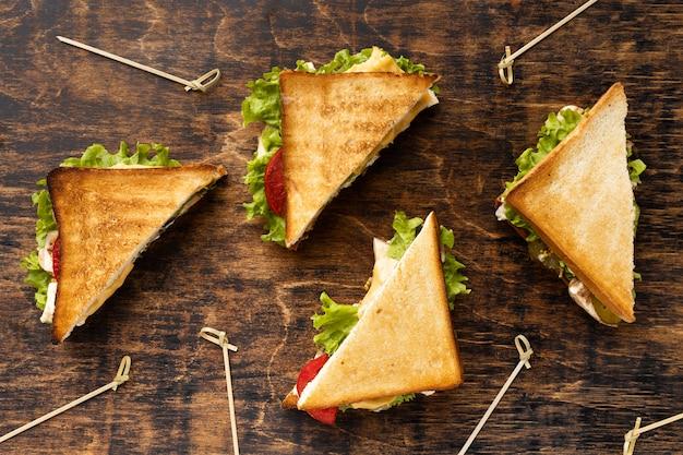Vista superior de quatro sanduíches triangulares com tomate e salada