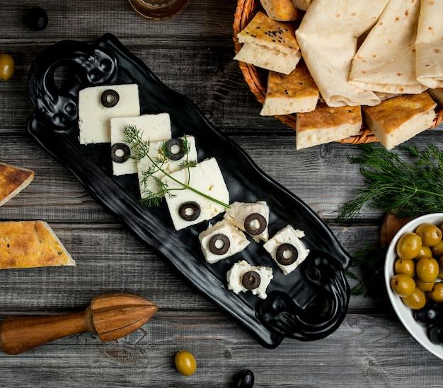 Vista superior de queijo branco e de cabra, coberto com fatias de azeitona