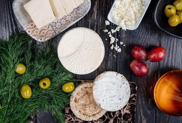 Vista superior de queijo de cabra com bolos de arroz com creme de queijo e endro com azeitonas em conserva e uvas doces em rústico