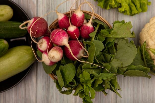 Vista superior de rabanetes orgânicos em um balde com pepinos e abobrinhas em um prato com alface e couve-flor isolada em uma superfície cinza de madeira