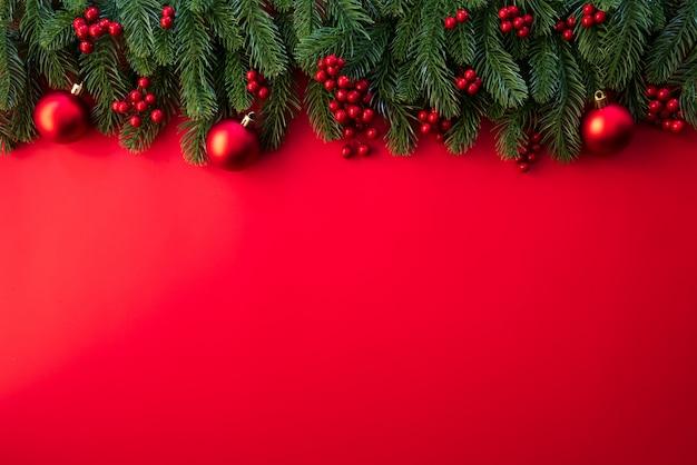Vista superior de ramos spruce do natal, cones do pinho, bagas vermelhas e sino no fundo vermelho.