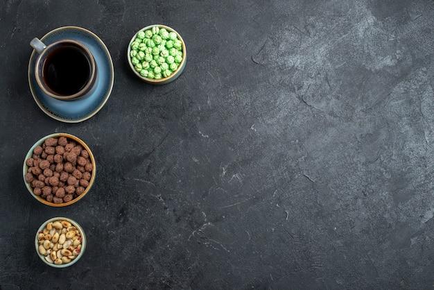Vista superior de rebuçados doces com uma xícara de café em fundo cinza escuro