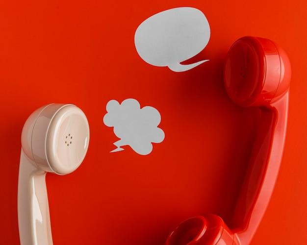 Vista superior de receptores de telefone com bolhas de bate-papo