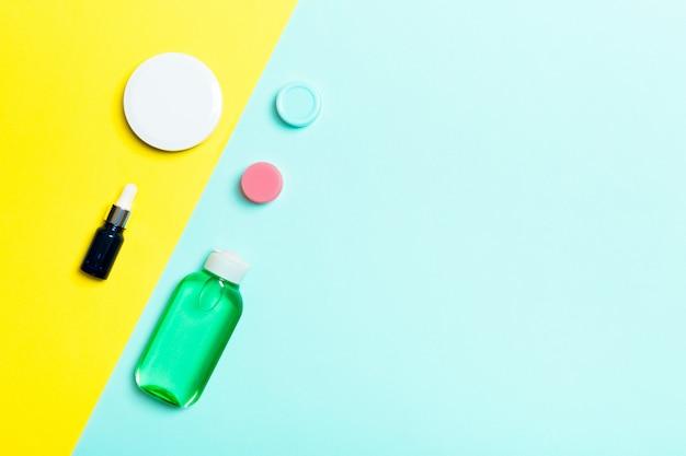 Vista superior de recipientes cosméticos, sprays, potes e garrafas em fundo amarelo e azul