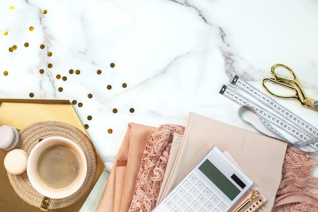 Vista superior de rendas coloridas coral dobradas e tecidos de seda com carretéis de linha, calculadora, bloco de notas, caneta, fita métrica, tesoura de costura perto de uma xícara de café com biscoitos de macarons na bandeja de ouro. copie o espaço