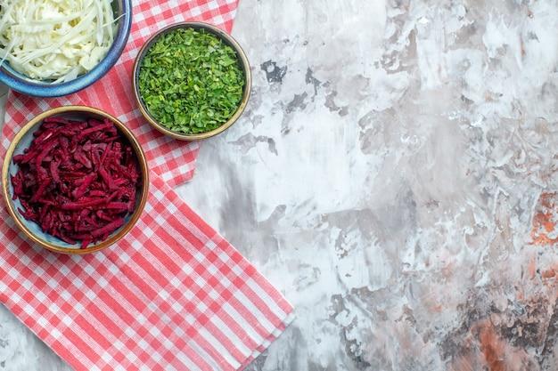 Vista superior de repolho fatiado com beterraba e verduras na superfície branca