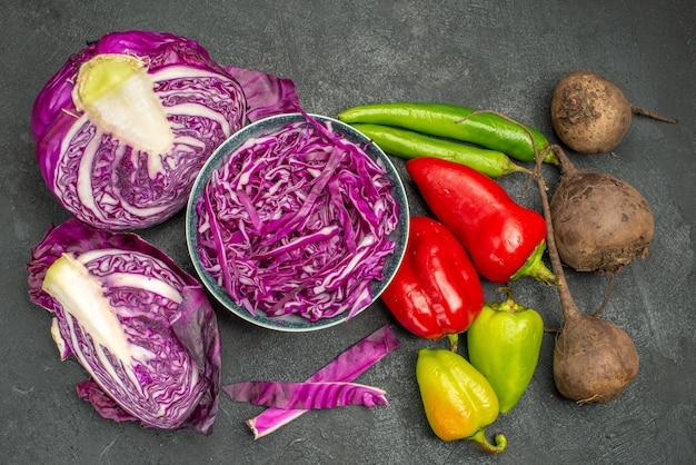 Vista superior de repolho roxo fatiado com legumes frescos em fundo escuro