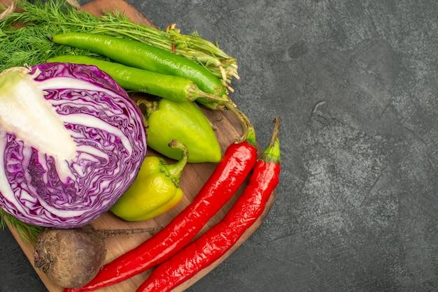 Vista superior de repolho roxo fatiado com outros vegetais em fundo escuro