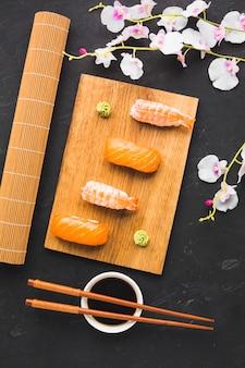 Vista superior de revestimento de sushi e flor de sakura