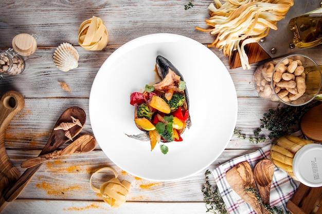 Vista superior de robalo cozido cheio de vegetais em um prato branco