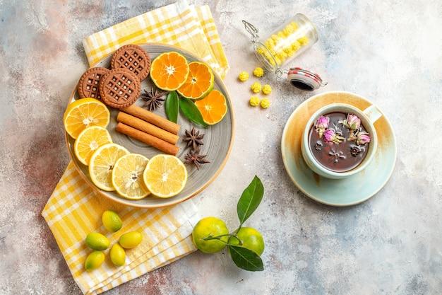 Vista superior de rodelas de limão, canela e limão em uma tábua de madeira e biscoitos na mesa branca