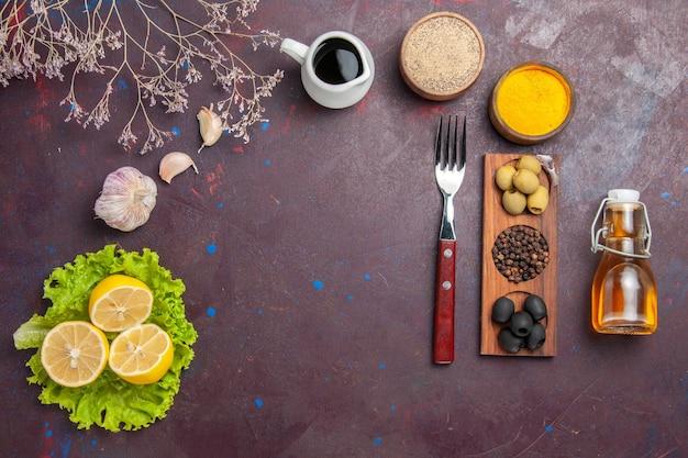 Vista superior de rodelas de limão frescas com salada verde no escuro Foto gratuita