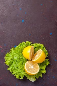 Vista superior de rodelas de limão frescas com salada verde no escuro