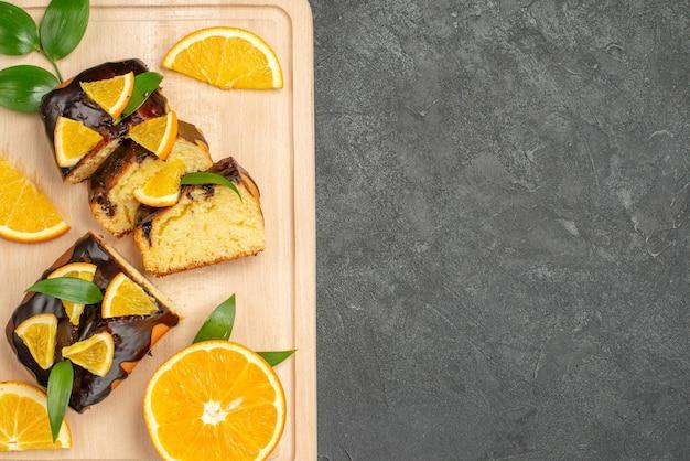 Vista superior de rodelas de limão fresco e fatias de bolo picadas em fundo escuro
