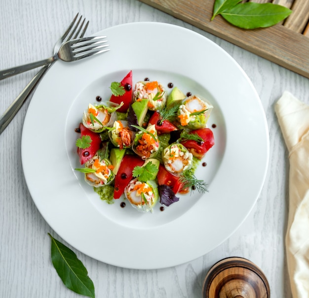 Vista superior de rolinhos primavera meio corte com camarão, alface servido com abacate
