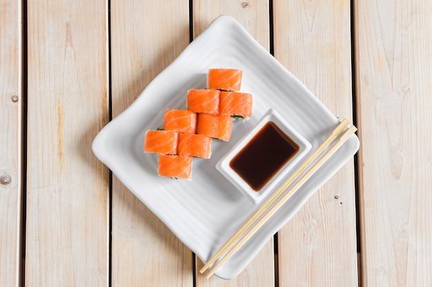 Vista superior de rolos com salada de truta e chuka na mesa de madeira