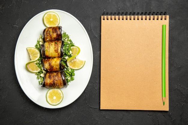 Vista superior de rolos de berinjela salgados prato cozido com rodelas de limão e bloco de notas na superfície escura do jantar com óleo para cozinhar prato