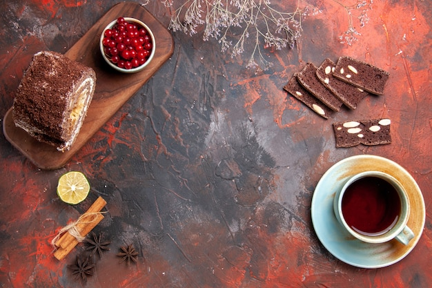 Vista superior de rolos de biscoito com xícara de chá na superfície escura