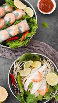 Vista superior de rolos de camarão com molho e limão
