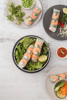 Vista superior de rolos de camarão fresco com salada e molho