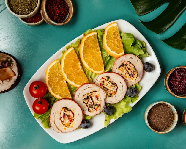 Vista superior de rolos de frango recheados com legumes e ervas, servidos com fatias de laranja e tomate cereja em uma bandeja