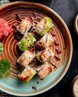 Vista superior de rolos de sushi com enguia abacate e pepino com gengibre e wasabi em um prato na madeira