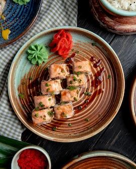 Vista superior de rolos de sushi com fatias de gengibre em salmão em conserva e wasabi num prato rústico