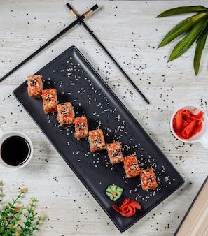 Vista superior de rolos de sushi com tobiko vermelho e gergelim