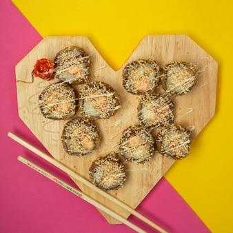 Vista superior de rolos de sushi frito em forma de coração com gengibre e wasabi