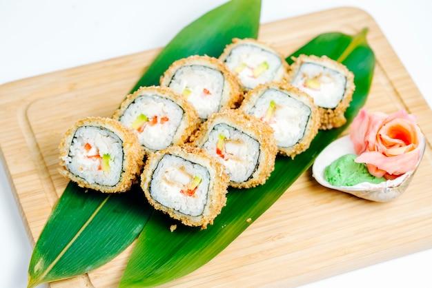 Vista superior de rolos quentes com tempura e abacate, servido na placa de madeira